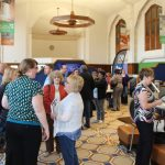People enjoying coffee in the Flint and Genesee Chamber lobby